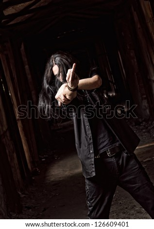 Portrait of long-haired young man making offensive gesture (middle finger) - stock photo