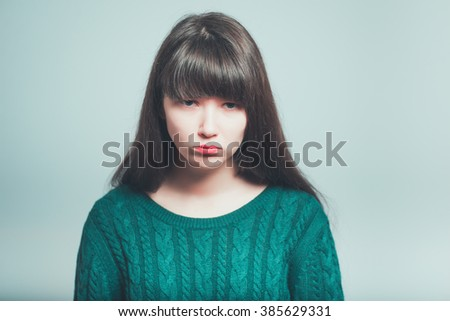 portrait of long-haired young woman was offended, isolated on a gray background - stock photo