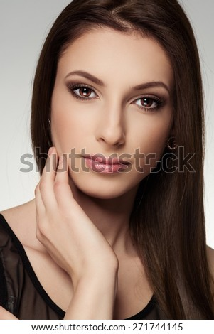 Portrait of long straight hair model with professional makeup. Young Caucasian lovely woman touching her clean healthy skin.   - stock photo