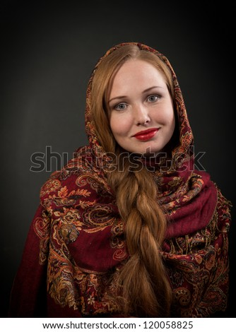 Portrait of looking at camera and smiling Slavonic girl with red braided hair, dark background