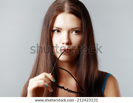 Portrait of looking up woman with hands on her glasses and looking at copyspace - stock photo