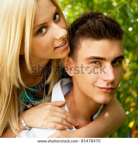 Portrait of love couple embracing outdoor in park looking happy