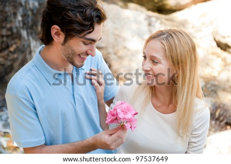 Portrait of love couple embracing outdoor in park looking happy. Man gifting flower to his girl