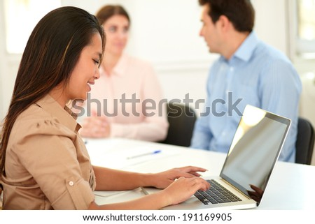 Portrait of lovely asiatic woman working on her laptop while sitting on workplace