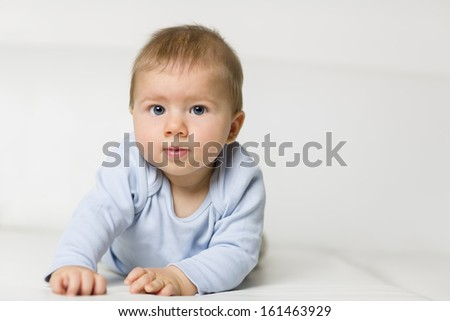 Portrait of lovely baby boy with blue eyes lying on his belly on white sofa.