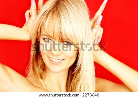 portrait of lovely blond with bunny ears gesture over red - stock photo