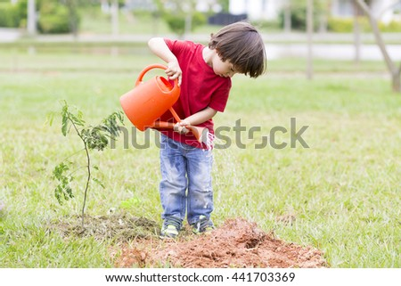 Portrait of Lovely Boy Watering Plants Outdoors