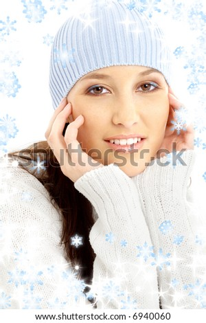 portrait of lovely brunette in winter hat with snowflakes
