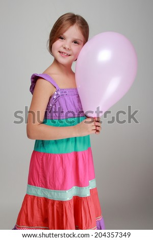 Portrait of lovely cheerful little girl with a sweet smile played with a balloon on gray background/Girl with a pink air balloon on Holiday