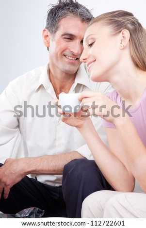 Portrait of lovely couple, woman holding cup.