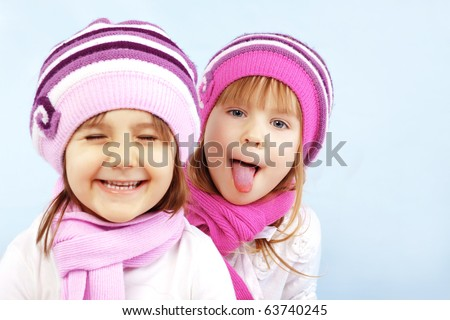 Portrait of lovely embracing kid girls wearing same winter clothing - stock photo