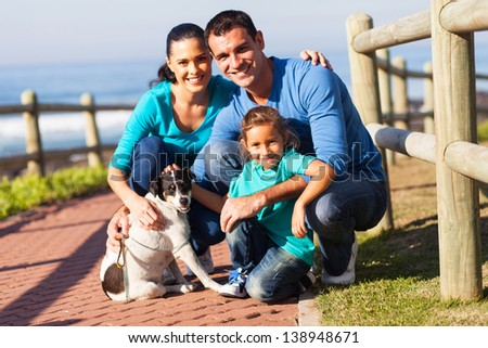 portrait of lovely family and pet dog outdoors at beach - stock photo
