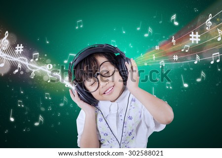 Portrait of lovely female child wearing glasses and smiling while listening music with headphones - stock photo
