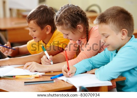 Portrait of lovely girl and her classmates drawing with highlighters at lesson - stock photo
