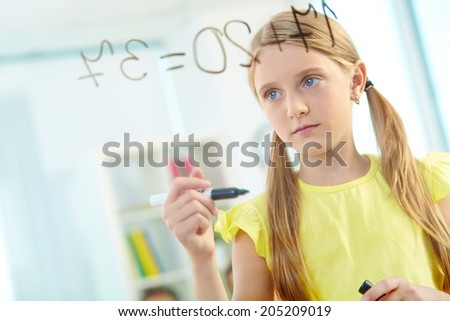 Portrait of lovely girl doing sums on transparent board at lesson - stock photo