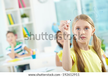 Portrait of lovely girl doing sums on transparent board with schoolmates on background - stock photo