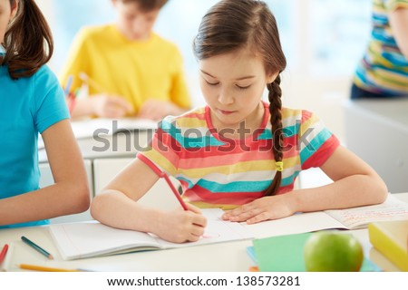 Portrait of lovely girl drawing at workplace surrounded by schoolmates - stock photo