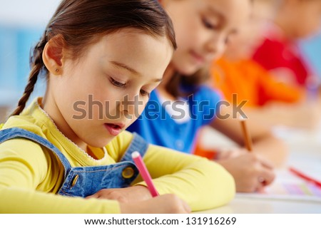 Portrait of lovely girl drawing at workplace with schoolmate on background - stock photo