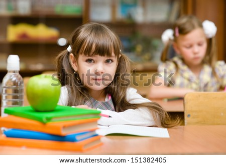 Portrait of lovely girl drawing in copybook and looking at camera