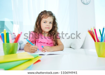 Portrait of lovely girl drawing with colorful pencils - stock photo