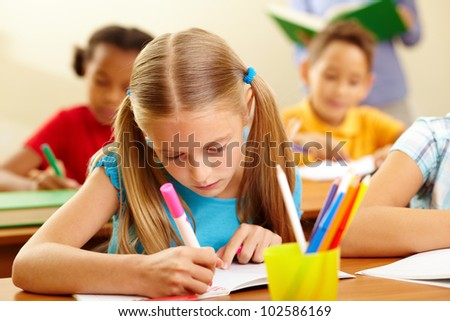 Portrait of lovely girl drawing with colorful pencils at lesson