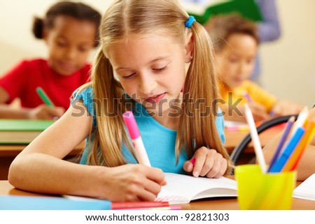Portrait of lovely girl drawing with colorful pencils at lesson - stock photo