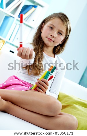 Portrait of lovely girl holding colorful pencils