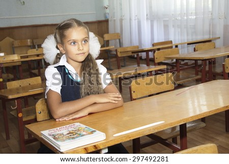 Portrait of lovely girl in classroom. schoolgirl at the desk, little schoolgirl sitting at an empty desk, class 2 exhaust, the girl raised her hand in class - stock photo