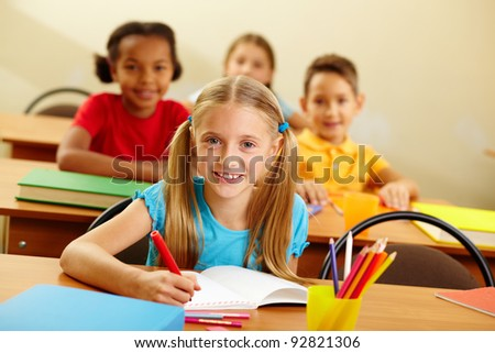 Portrait of lovely girl looking at camera at lesson - stock photo