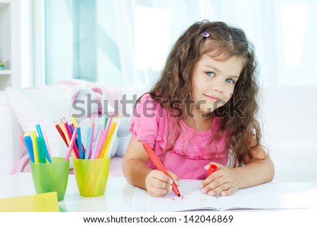 Portrait of lovely girl looking at camera while drawing with colorful pencils - stock photo