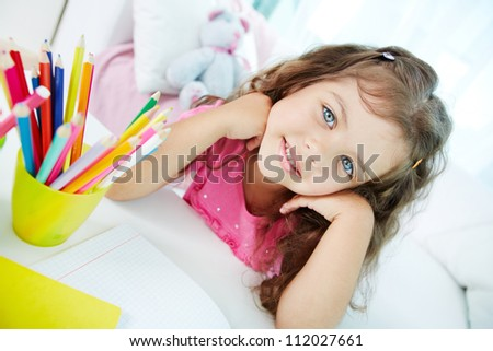 Portrait of lovely girl looking at camera with colorful pencils near by - stock photo