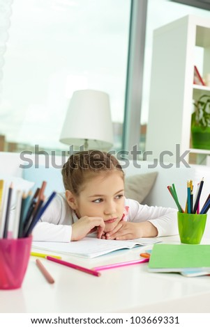 Portrait of lovely girl thinking of what to draw at leisure