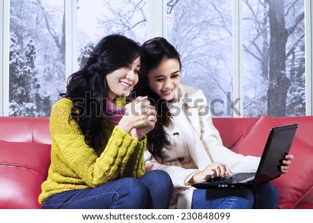Portrait of lovely girls using laptop together while wearing winter clothes and sitting on sofa at home - stock photo