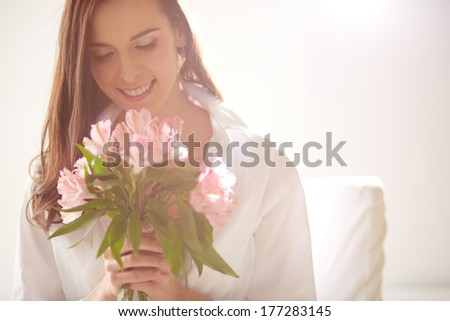 Portrait of lovely lady looking at bunch of pink lilies in her hands