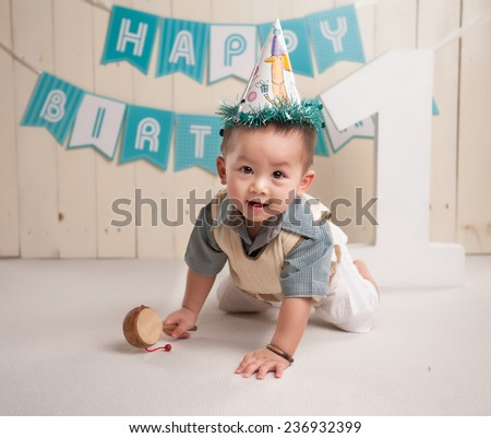 Portrait of lovely little boy crawling happy smiling with 1 year wooden letter word. One year old Asian boy sitting on floor - stock photo