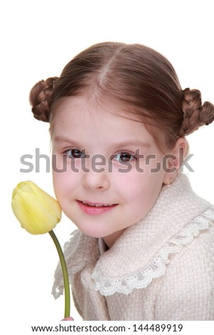 portrait of lovely little girl wearing coat and holding lovely single yellow tulip on Holiday theme/smiley beautiful girl with nice hairstyle