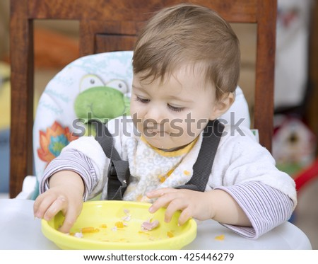 Portrait of lovely one year old baby eating with hands