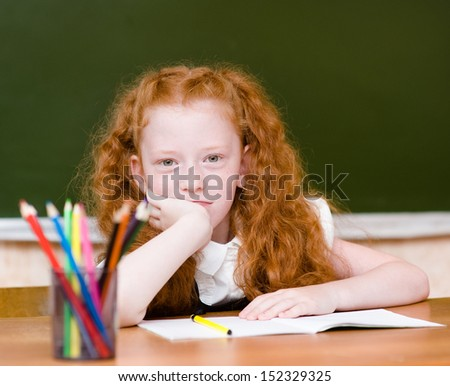 Portrait of lovely schoolgirl looking at camera