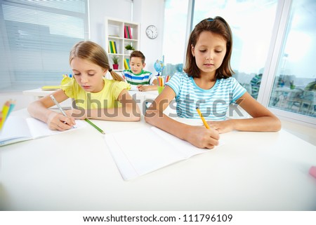 Portrait of lovely schoolgirls drawing at workplace with schoolmate on background - stock photo