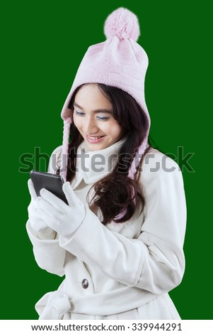 Portrait of lovely teenage girl wearing winter fashion and texting with a smartphone, shot in studio against green background - stock photo