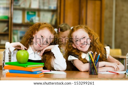 Portrait of lovely twins girls with schoolgirl on background. looking at camera - stock photo