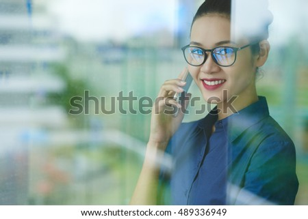 Portrait of lovely Vietnamese business lady talking on phone