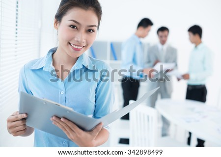 Portrait of lovely Vietnamese business lady with a folder - stock photo