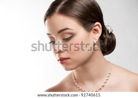 Portrait of lovely woman with beautiful make-up and hairstyle. Elegant woman with pearl jewelry