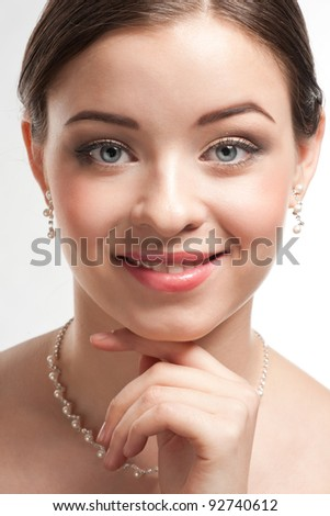 Portrait of lovely woman with beautiful make-up smiling. Elegant woman with pearl jewelry