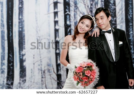 Portrait of lovely  young bride and groom looking for something - stock photo