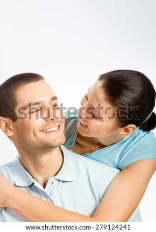 Portrait of lovely young couple, with copyspace blank area for text or slogan, on grey background - stock photo