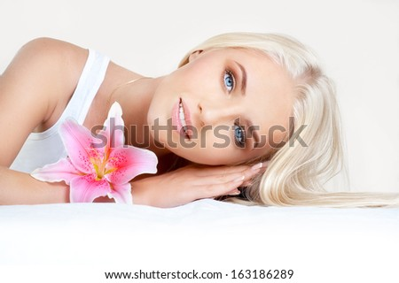 Portrait of lovely young girl with flower on light gray background