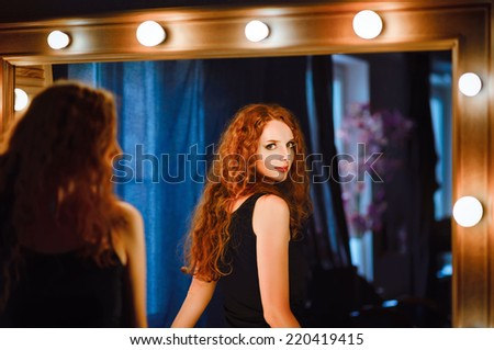 Portrait of lovely young redhead woman looking into the mirror - stock photo