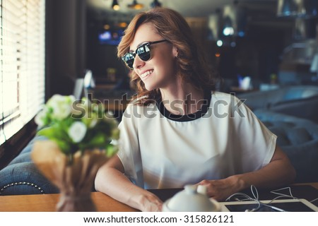 Portrait of lovely young woman dressed in stylish sunglasses looking out coffee shop window with bright smile, happy attractive female waiting for her friends while sitting in modern cafe interior - stock photo